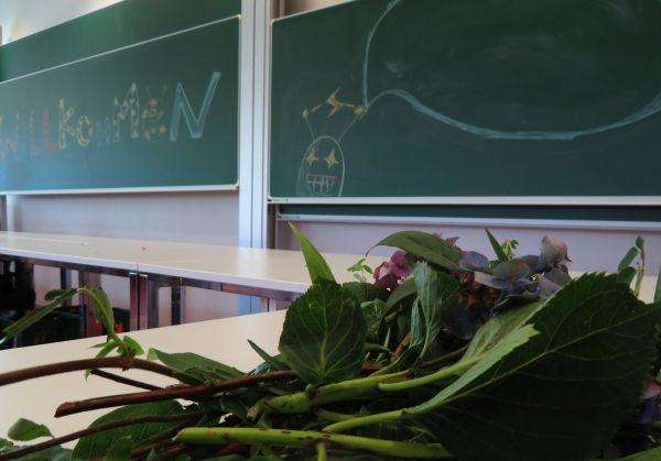 Herzlich-Willkommen-Tafel mit Blumen in der Sommeruni-Cafeteria