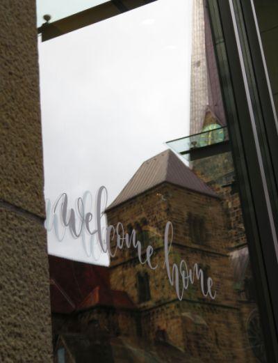 welcome-home-Schriftzug auf Fenster, in dem sich ein Teil des Doms spiegelt