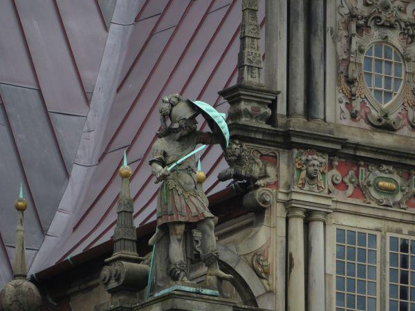 Kleiner kriegerischer Mann (Statue) hält sein Schild schützend vor seinen Kopf