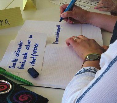 Teilnehmerin schreibt Moderationskarte