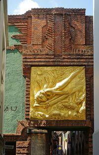 Goldenes Relief über dem Eingang zur schmalen Böttcherstraßen mit kleinen Läden und Kunst