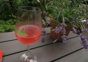 Gartentisch mit Grapefruitschorle, Lavendelstrauß und Buchrücken