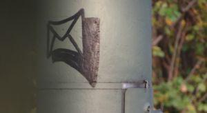 Briefumschlag-Graffito auf einem Laternenpfahl